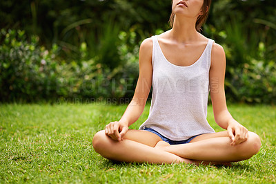 Buy stock photo A young woman meditating in the garden