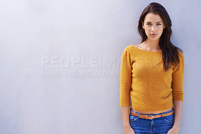Buy stock photo Portrait of a beautiful young woman standing confidently against a gray wall
