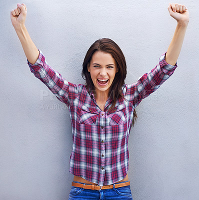 Buy stock photo Shot of an attractive young woman with her arms raised in celebration