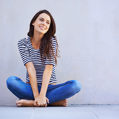 Buy stock photo A beautiful young woman looking thoughtful while sitting cross-legged on the floor