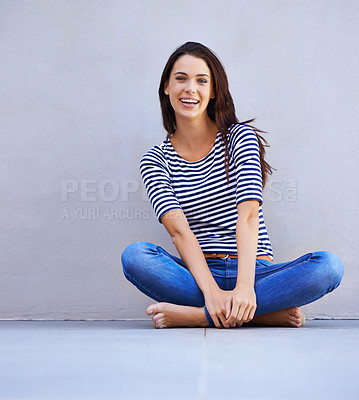 Buy stock photo Portrait of a beautiful young woman sitting with her legs crossed on the floor