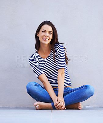 Buy stock photo Full-length shot of a beautiful young woman sitting cross-legged on the floor