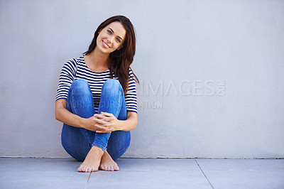 Buy stock photo Full-length portrait of a beautiful young woman hugging her knees while sitting on the floor