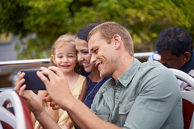 Buy stock photo Shot of a young father showing his wife and daughter something on his phone