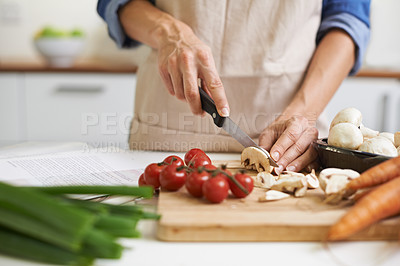 Buy stock photo A young woman chopping vegetables