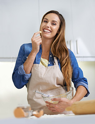 Buy stock photo A young woman smiling as she tastes the batter she's prepared