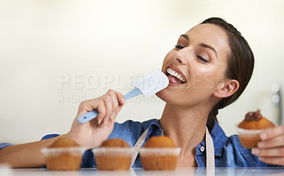 Buy stock photo A happy young woman licking frosting off a spatula