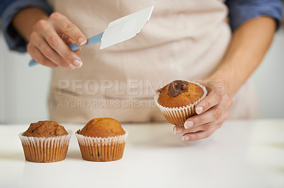 Buy stock photo A closeup image of a woman applying frosting to a cupcake