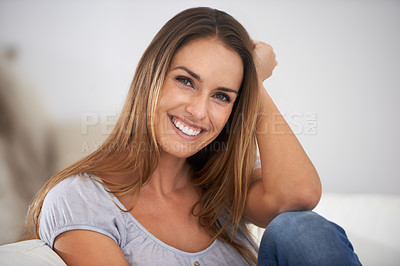 Buy stock photo Cropped shot of a beautiful young woman on her living room sofa