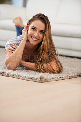 Buy stock photo Portait of a cheerful woman lying on her living room carpet