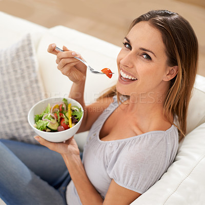 Buy stock photo Portrait of a beautiful woman eating a salad from the comfort of her couch