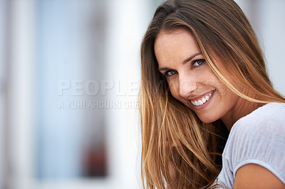 Buy stock photo Portrait of a beautiful young woman smiling at the camera while sitting outside