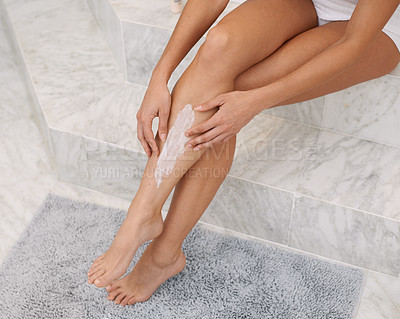 Buy stock photo Cropped shot of a woman applying hair removal cream to her legs