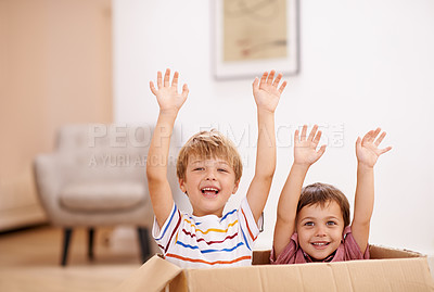 Buy stock photo Two young brothers raising their arms as they jump out of a cardboard box
