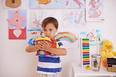 Buy stock photo A young boy possessively clasping his toy truck to his chest