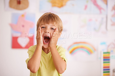 Buy stock photo A young boy cupping his face while screaming