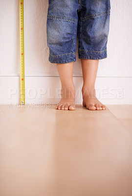 Buy stock photo Cropped shot of a young boy standing next to a tape measure