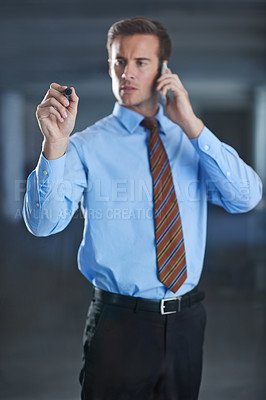 Buy stock photo Cropped shot of a handsome young businessman writing with a marker while talking on his cellphone