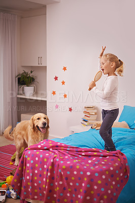 Buy stock photo A little girl jumping on her bed and singing into her hairbrush while her dog watches