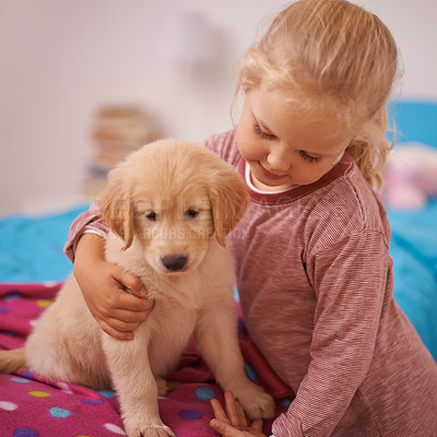 Buy stock photo A cropped shot of a little girl holding her puppy while it sits on her bed