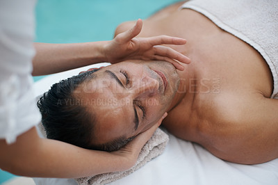 Buy stock photo Cropped shot of a handsome man enjoying a massage at the spa