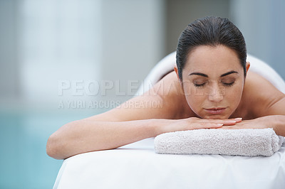 Buy stock photo Shot of a beautiful woman lying on a poolside massage table