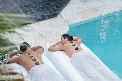 Buy stock photo High angle shot of a couple enjoying a hot stone massage