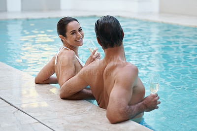 Buy stock photo Cropped shot of a couple drinking champagne poolside