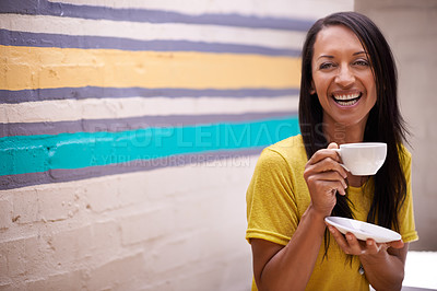 Buy stock photo Shot of an attractive woman drinking tea with a colorful wall behind her