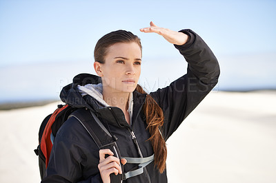 Buy stock photo Shot of an attractive young woman walking along the sand dunes