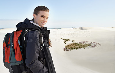 Buy stock photo Portrait of a young female hiker walking along the sand dunes
