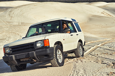 Buy stock photo Shot of a heavy duty 4x4 driving along some sand dunes