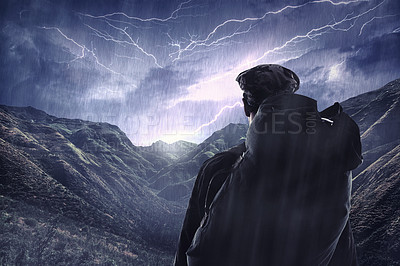 Buy stock photo Shot of a hiker watching a thunderstorm over a mountain