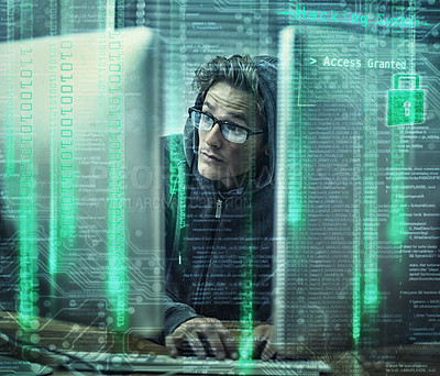 Buy stock photo Shot of a young man wearing hoodie while hacking into a computer