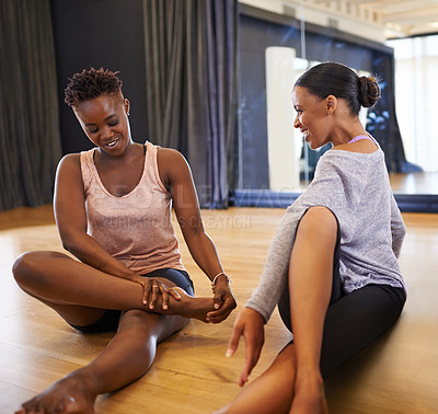 Buy stock photo Shot of two young women dancers stretching on the floor