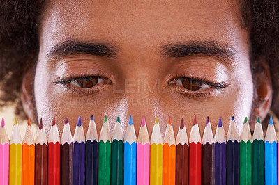 Buy stock photo Cropped view of an african man looking closely at a row of colorful pencil crayons