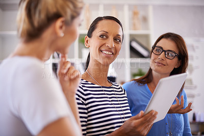 Buy stock photo Three businesswomen brainstorming ideas while gathered around a digital tablet