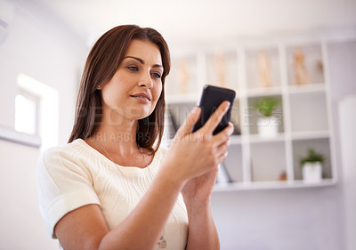 Buy stock photo A happy young woman sending a text message