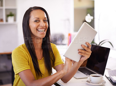 Buy stock photo A young businesswoman smiling happily as she holds a digital tablet