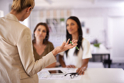 Buy stock photo Rear-view shot of a female architect explaining something to two of her colleagues