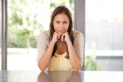 Buy stock photo A happy young woman smiling at the camera while sitting at home