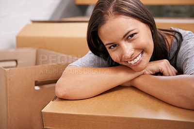 Buy stock photo A beautiful young woman smiling at the camera surrounded by boxes in her new home