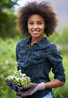Buy stock photo Portrait of a happy young woman holding a tray of seedlings in a garden