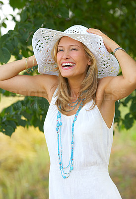 Buy stock photo Flirtatious portrait of a gorgeous woman wearing a summer hat and laughing