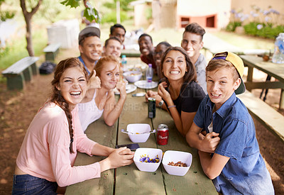 Buy stock photo Shot of a group of teenagers having a picnic at a table in the park