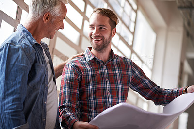 Buy stock photo Shot of two male architects standing with blueprints inside a building