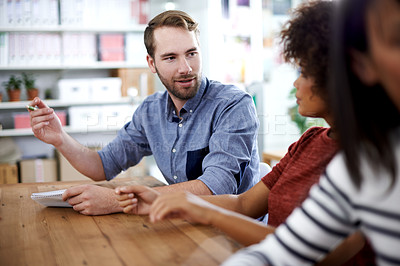 Buy stock photo Shot of a handsome young  businessman sharing his ideas in a meeting