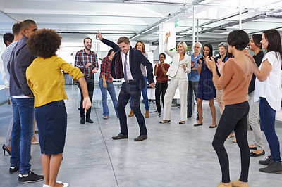 Buy stock photo Shot of a businessman in a suit dancing in the office to cheers from coworkers
