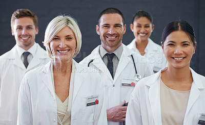Buy stock photo Studio portrait of a team of doctors standing against a grey background