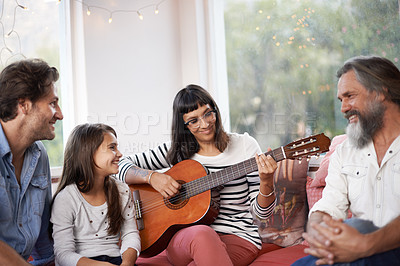 Buy stock photo Shot of a woman playing the guitar while sitting with her family